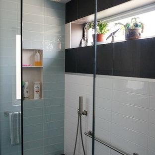 Idee per una piccola stanza da bagno padronale minimal con ante lisce, ante in legno chiaro, doccia aperta, WC monopezzo, piastrelle grigie, piastrelle di vetro, pareti grigie, pavimento in gres porcellanato, lavabo sottopiano, top in quarzo composito, pavimento nero e porta doccia a battente