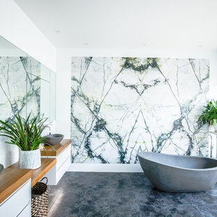 This is an example of a contemporary bathroom in Sydney with flat-panel cabinets, white cabinets, a freestanding tub, white walls, a vessel sink, wood benchtops, black floor and brown benchtops.