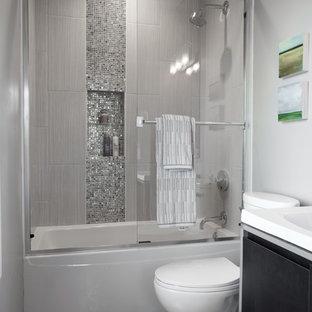 Imagen de cuarto de baño contemporáneo, pequeño, con lavabo tipo consola, armarios con paneles lisos, puertas de armario de madera en tonos medios, encimera de acrílico, bañera empotrada, ducha empotrada, baldosas y/o azulejos grises, baldosas y/o azulejos de vidrio, paredes grises y suelo de baldosas de cerámica