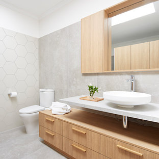 Photo of a contemporary bathroom in Melbourne with flat-panel cabinets, light wood cabinets, grey walls and a vessel sink.