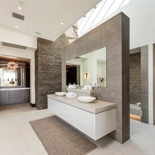 Modelo de cuarto de baño principal, contemporáneo, con armarios con paneles lisos, puertas de armario blancas, ducha abierta, baldosas y/o azulejos marrones, baldosas y/o azulejos grises, baldosas y/o azulejos de piedra, paredes blancas, lavabo sobreencimera, suelo blanco, ducha abierta y encimeras beige