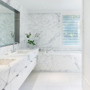 Design ideas for a contemporary ensuite bathroom in Boston with an integrated sink, flat-panel cabinets, white cabinets, a submerged bath, multi-coloured tiles and marble tiles.