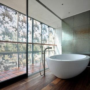 Idée de décoration pour une salle de bain design avec une baignoire indépendante et un sol en bois foncé.