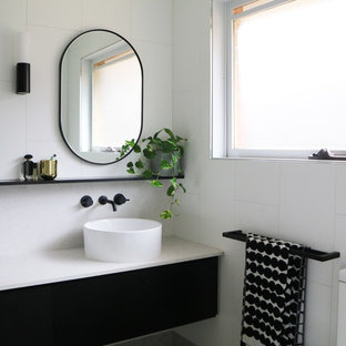 Design ideas for a large contemporary bathroom in Melbourne with flat-panel cabinets, black cabinets, white tile, white walls, a vessel sink, grey floor, white benchtops, an open shower, ceramic tile, pebble tile floors and engineered quartz benchtops.