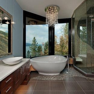 Inredning av ett modernt badrum, med skåp i mörkt trä, ett fristående badkar, en hörndusch, grå kakel, kakel i småsten, klinkergolv i småsten och blå väggar