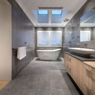 Ejemplo de cuarto de baño principal, actual, con armarios con paneles lisos, puertas de armario de madera clara, bañera japonesa, ducha abierta, baldosas y/o azulejos grises, paredes marrones, lavabo sobreencimera, suelo gris y ducha abierta