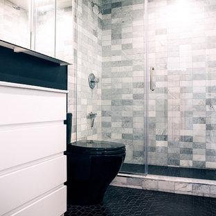 Idee per una piccola stanza da bagno padronale design con ante lisce, ante bianche, doccia ad angolo, WC monopezzo, piastrelle grigie, piastrelle di marmo, pareti nere, pavimento con piastrelle in ceramica, lavabo integrato, pavimento nero, porta doccia a battente e top bianco