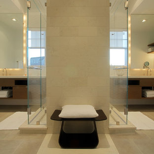 Example of a trendy beige tile and limestone tile alcove shower design in Other with flat-panel cabinets and dark wood cabinets