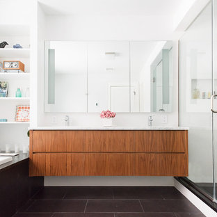 Large trendy master black floor bathroom photo in New York with flat-panel cabinets, medium tone wood cabinets, white walls, an undermount sink, marble countertops, a hinged shower door and gray countertops