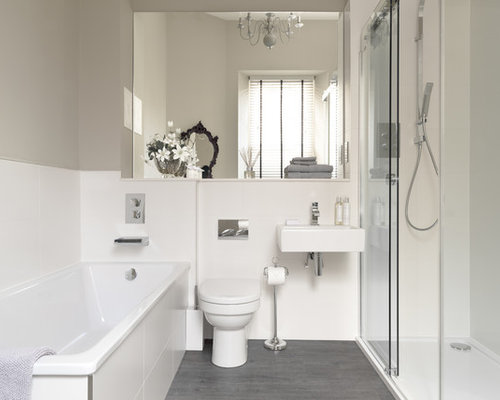 tub an alcove shower gray walls a one piece toilet and gray floors