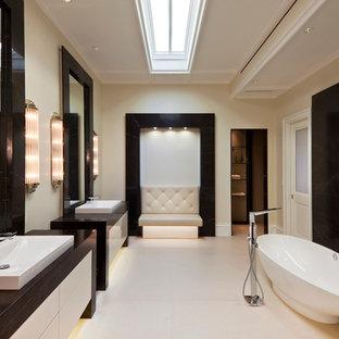 Modelo de cuarto de baño actual con lavabo de seno grande, encimera de granito, bañera exenta, baldosas y/o azulejos negros, losas de piedra y paredes blancas