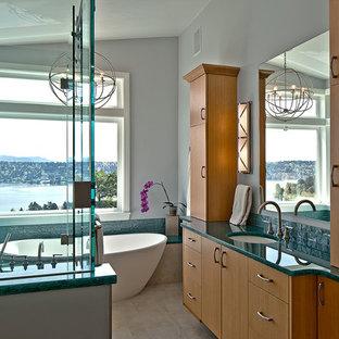 Foto på ett maritimt en-suite badrum, med ett undermonterad handfat, släta luckor, skåp i ljust trä, bänkskiva i återvunnet glas, ett fristående badkar, en öppen dusch och klinkergolv i porslin