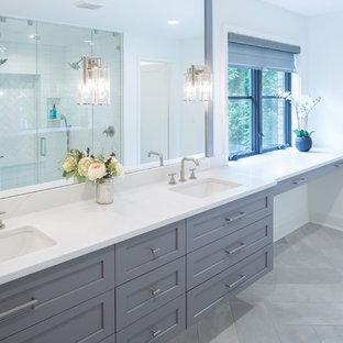 グランドラピッズの広いコンテンポラリースタイルのおしゃれなマスターバスルーム (シェーカースタイル扉のキャビネット、グレーのキャビネット、ミラータイル、白い壁、セラミックタイルの床、アンダーカウンター洗面器、クオーツストーンの洗面台、グレーの床、白い洗面カウンター) の写真