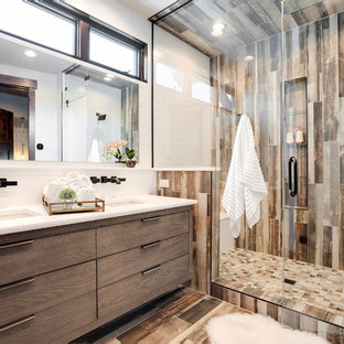 Trendy 3/4 brown floor alcove shower photo in Denver with flat-panel cabinets, medium tone wood cabinets, white walls, an undermount sink, a hinged shower door and white countertops