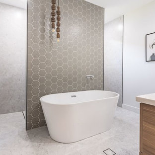 Bathroom - large contemporary master gray tile and mosaic tile terrazzo floor and white floor bathroom idea in Newcastle - Maitland with recessed-panel cabinets, medium tone wood cabinets, a two-piece toilet, gray walls, a wall-mount sink and engineered quartz countertops