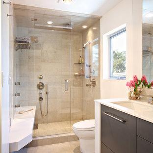 Modelo de cuarto de baño contemporáneo con lavabo bajoencimera, armarios con paneles lisos, puertas de armario de madera en tonos medios, baldosas y/o azulejos beige y baldosas y/o azulejos de piedra caliza