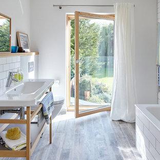 Ejemplo de cuarto de baño actual, de tamaño medio, con suelo de baldosas de cerámica, armarios abiertos, puertas de armario de madera clara, baldosas y/o azulejos de cerámica, combinación de ducha y bañera, sanitario de pared, lavabo tipo consola, paredes blancas y baldosas y/o azulejos blancos