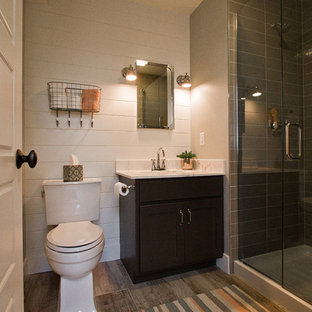 Corner shower - small craftsman 3/4 vinyl floor and brown floor corner shower idea in Other with recessed-panel cabinets, black cabinets, a two-piece toilet, white walls, a drop-in sink, marble countertops and a hinged shower door