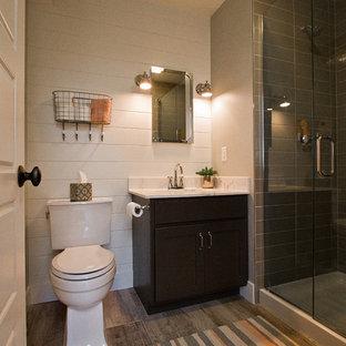 Modelo de cuarto de baño con ducha, de estilo americano, pequeño, con armarios con paneles empotrados, puertas de armario negras, ducha esquinera, sanitario de dos piezas, paredes blancas, suelo vinílico, lavabo encastrado, encimera de mármol, suelo marrón y ducha con puerta con bisagras