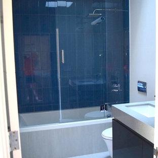 Ejemplo de cuarto de baño principal, contemporáneo, de tamaño medio, con armarios con paneles lisos, bañera esquinera, combinación de ducha y bañera, sanitario de una pieza, paredes blancas, lavabo bajoencimera, puertas de armario de madera en tonos medios y encimera de esteatita