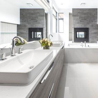 Exempel på ett stort modernt vit vitt en-suite badrum, med släta luckor, grå skåp, ett undermonterat badkar, vita väggar, ett fristående handfat, vitt golv, en dusch i en alkov, brun kakel, keramikplattor, klinkergolv i porslin, bänkskiva i akrylsten och dusch med gångjärnsdörr