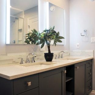 バンクーバーの中くらいのコンテンポラリースタイルのおしゃれなマスターバスルーム (シェーカースタイル扉のキャビネット、濃色木目調キャビネット、置き型浴槽、コーナー設置型シャワー、分離型トイレ、白いタイル、モザイクタイル、グレーの壁、クッションフロア、アンダーカウンター洗面器、クオーツストーンの洗面台) の写真