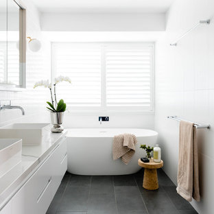 Inspiration for a beach style bathroom in Brisbane with flat-panel cabinets, white cabinets, a freestanding tub, white walls, a vessel sink, grey floor and white benchtops.
