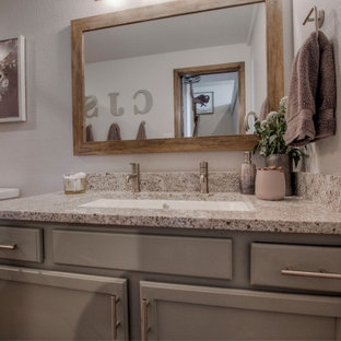 Photo of a country family bathroom in Denver with shaker cabinets, green cabinets, an alcove bath, a shower/bath combination, a two-piece toilet, beige tiles, porcelain tiles, grey walls, laminate floors, a trough sink, granite worktops, brown floors, a shower curtain, beige worktops, a single sink and a built in vanity unit.