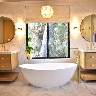 Foto de cuarto de baño principal, actual, con puertas de armario de madera oscura, bañera exenta, lavabo integrado, encimeras blancas, armarios con paneles lisos, baldosas y/o azulejos beige, paredes beige, suelo de madera clara y suelo beige