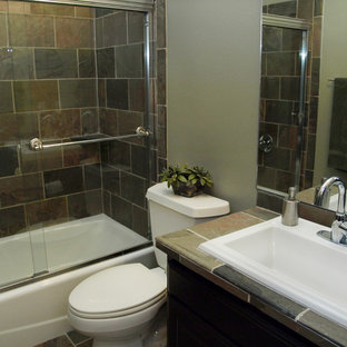 Inspiration for a small contemporary beige tile, gray tile and slate tile slate floor bathroom remodel in Austin with flat-panel cabinets, a two-piece toilet, a drop-in sink, tile countertops, brown cabinets and gray walls