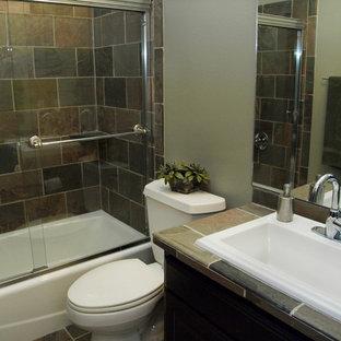 Imagen de cuarto de baño contemporáneo, pequeño, con armarios con paneles lisos, bañera empotrada, combinación de ducha y bañera, sanitario de dos piezas, baldosas y/o azulejos beige, baldosas y/o azulejos grises, baldosas y/o azulejos de pizarra, suelo de pizarra, lavabo encastrado, encimera de azulejos, puertas de armario marrones y paredes grises