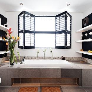 Diseño de cuarto de baño contemporáneo con bañera encastrada, baldosas y/o azulejos grises, suelo de baldosas tipo guijarro y paredes negras