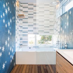 Imagen de cuarto de baño principal, contemporáneo, de tamaño medio, con armarios con paneles lisos, puertas de armario de madera clara, bañera empotrada, combinación de ducha y bañera, sanitario de una pieza, baldosas y/o azulejos multicolor, baldosas y/o azulejos de cemento, paredes blancas, suelo de baldosas de porcelana, lavabo suspendido, encimera de cuarzo compacto, suelo negro y ducha abierta
