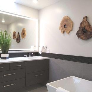 Immagine di una stanza da bagno padronale design di medie dimensioni con ante grigie, vasca freestanding, piastrelle grigie, piastrelle in ardesia, pareti bianche, pavimento in laminato, pavimento beige e top bianco
