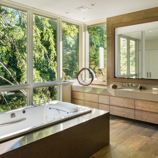Drop-in bathtub - contemporary brown tile drop-in bathtub idea in New York with an undermount sink, flat-panel cabinets, medium tone wood cabinets and brown countertops