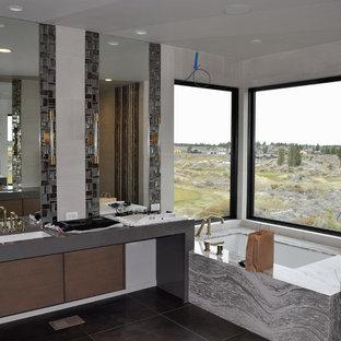 Modelo de cuarto de baño principal, contemporáneo, grande, con armarios con paneles lisos, puertas de armario marrones, bañera esquinera, ducha abierta, sanitario de una pieza, baldosas y/o azulejos grises, baldosas y/o azulejos de vidrio, paredes grises, suelo de baldosas de cerámica, lavabo bajoencimera, encimera de granito, suelo marrón, ducha abierta y encimeras grises