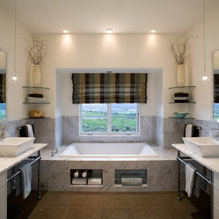 Transitional gray tile and porcelain tile ceramic floor and brown floor drop-in bathtub photo in Denver with flat-panel cabinets, white cabinets, marble countertops, a vessel sink, beige walls and white countertops