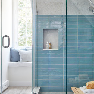 Example of a mid-sized trendy master blue tile and ceramic tile porcelain tile and gray floor corner shower design in Boston with glass-front cabinets, blue cabinets, a two-piece toilet, white walls, a wall-mount sink, quartz countertops and a hinged shower door