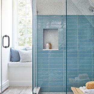 Foto på ett mellanstort funkis en-suite badrum, med luckor med glaspanel, blå skåp, en hörndusch, en toalettstol med separat cisternkåpa, blå kakel, keramikplattor, vita väggar, klinkergolv i porslin, ett väggmonterat handfat, bänkskiva i kvarts, grått golv och dusch med gångjärnsdörr