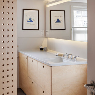 This is an example of a small contemporary kids bathroom in London with flat-panel cabinets, light wood cabinets, a drop-in tub, a shower/bathtub combo, a wall-mount toilet, gray tile, ceramic tile, grey walls, ceramic floors, a drop-in sink, solid surface benchtops, grey floor, a shower curtain, grey benchtops, a laundry, a single vanity, a built-in vanity and panelled walls.