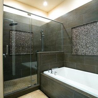 ヒューストンの大きいコンテンポラリースタイルのおしゃれなマスターバスルーム (フラットパネル扉のキャビネット、中間色木目調キャビネット、ドロップイン型浴槽、アルコーブ型シャワー、一体型トイレ、グレーのタイル、磁器タイル、グレーの壁、クッションフロア、オーバーカウンターシンク、御影石の洗面台) の写真