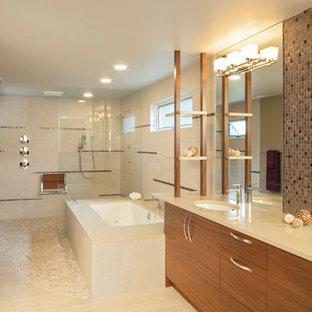 ポートランドの大きいコンテンポラリースタイルのおしゃれなマスターバスルーム (アンダーカウンター洗面器、フラットパネル扉のキャビネット、中間色木目調キャビネット、珪岩の洗面台、アンダーマウント型浴槽、バリアフリー、分離型トイレ、ベージュのタイル、磁器タイル、ベージュの壁、玉石タイル) の写真
