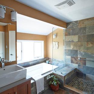 Imagen de cuarto de baño principal, clásico renovado, de tamaño medio, con armarios estilo shaker, puertas de armario de madera en tonos medios, bañera encastrada, ducha esquinera, baldosas y/o azulejos multicolor, baldosas y/o azulejos de piedra, paredes amarillas, lavabo sobreencimera y encimera de cemento