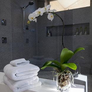 Inspiration för ett mellanstort funkis en-suite badrum, med öppna hyllor, grå skåp, ett fristående badkar, en öppen dusch, grå kakel, flerfärgad kakel, spegel istället för kakel, grå väggar, klinkergolv i keramik, ett integrerad handfat och bänkskiva i akrylsten