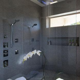 Modelo de cuarto de baño principal, actual, de tamaño medio, con armarios abiertos, puertas de armario grises, bañera exenta, ducha abierta, baldosas y/o azulejos grises, baldosas y/o azulejos multicolor, baldosas y/o azulejos con efecto espejo, paredes grises, suelo de baldosas de cerámica, lavabo integrado y encimera de acrílico