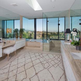 Immagine di un'ampia stanza da bagno padronale minimal con ante lisce, ante bianche, vasca sottopiano, doccia ad angolo, piastrelle beige, piastrelle di pietra calcarea, pavimento in gres porcellanato, lavabo sottopiano e top in pietra calcarea