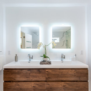 Large trendy master white tile and porcelain tile porcelain tile and white floor bathroom photo in Los Angeles with flat-panel cabinets, medium tone wood cabinets, white walls, a two-piece toilet, an integrated sink, quartz countertops, a hinged shower door and white countertops