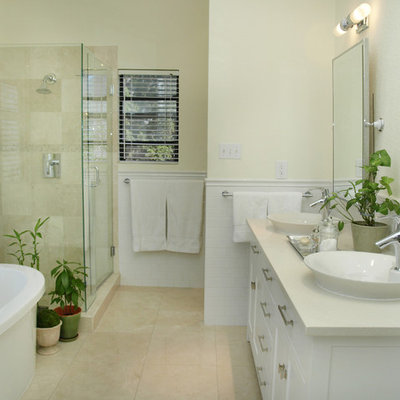 Inspiration for a mid-sized timeless master travertine tile, beige tile and white tile travertine floor freestanding bathtub remodel in Austin with shaker cabinets, white cabinets, a vessel sink, beige walls and marble countertops