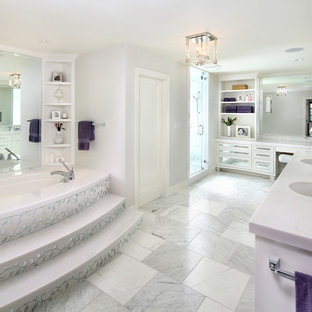 Large transitional master white tile and mirror tile marble floor bathroom photo in San Francisco with an undermount sink, white cabinets, marble countertops, an undermount tub, gray walls and glass-front cabinets