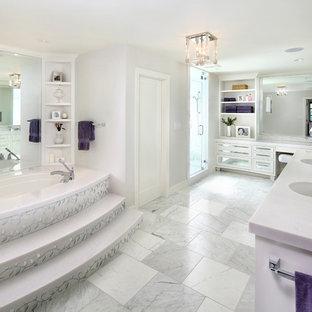Diseño de cuarto de baño principal, tradicional renovado, grande, con lavabo bajoencimera, puertas de armario blancas, encimera de mármol, bañera encastrada sin remate, baldosas y/o azulejos blancos, baldosas y/o azulejos con efecto espejo, paredes grises, suelo de mármol y armarios tipo vitrina